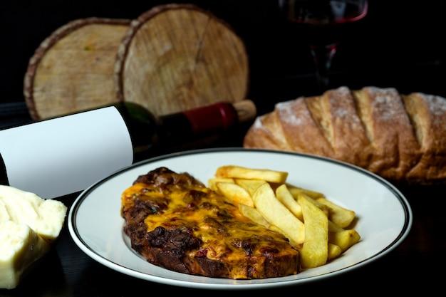 Bife coberto com queijo derretido, servido com batata frita