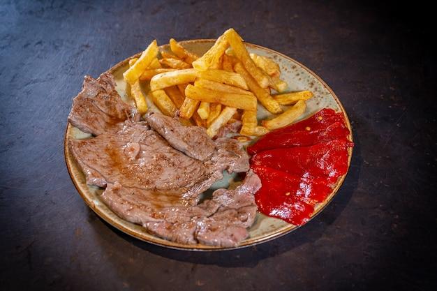 Bife com batata e pimentão vermelho em um fundo preto, em um prato branco