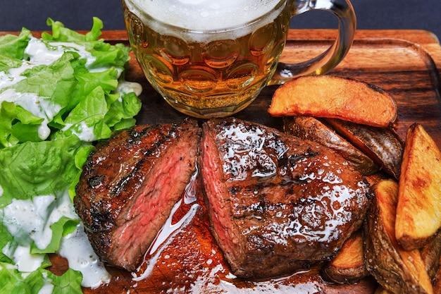 Bife com batata frita e um copo de cerveja em uma tábua de madeira