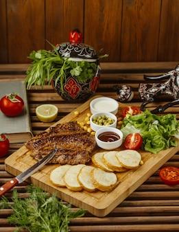 Bife com batatas assadas redondas em uma mesa de madeira, vista lateral, com salada verde, feijão e maionese