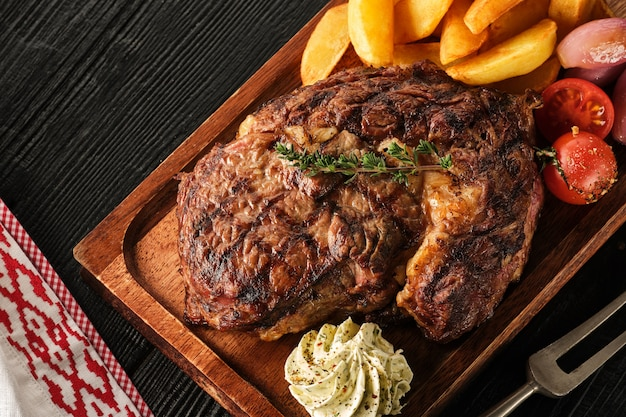 Bife com batatas, cebolas e tomates cereja assados. bife suculento com manteiga aromatizada