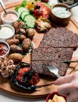 Bife com batatas fritas e legumes na placa de madeira