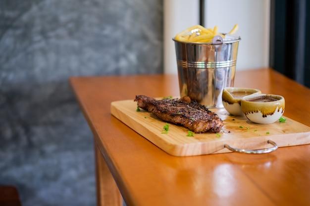 Bife com batatas fritas e molho em uma bandeja de madeira
