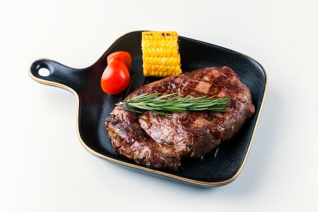 Bife com legumes e alecrim em uma tigela sobre fundo branco. vista do topo.