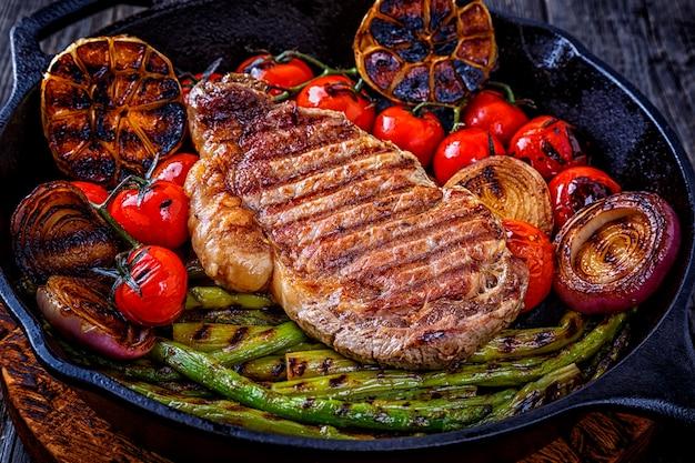 Bife com legumes grelhados em uma frigideira.