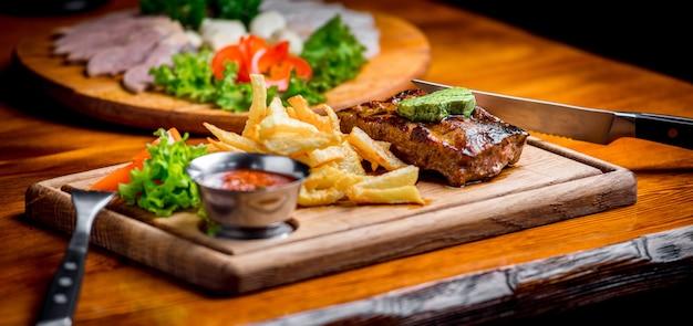 Bife com molho de pimenta e legumes grelhados na tábua