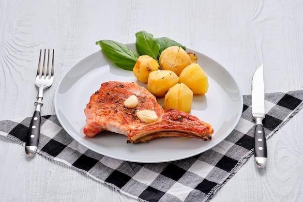 Bife com osso e batata assada no forno em uma assadeira com alho e tomilho