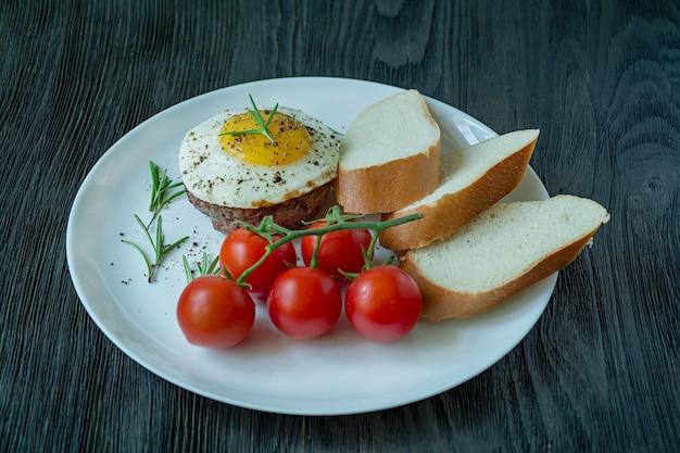 Bife com ovo frito em especiarias decorado com alecrim, cereja fresca e fatias de pão. arquivado em um prato branco. de madeira escura. vista lateral.