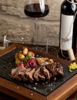 Bife cortado com batatas e ervas cozidas e um copo de vinho tinto