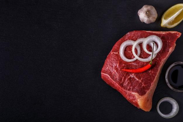 Bife cru com especiarias e ingredientes para cozinhar.