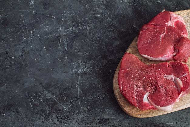 Bife cru de carne crua fresca isolado fundo escuro de concreto vista superior espaço da cópia postura plana