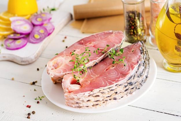 Bife cru de peixe carpa com limão e tomilho na mesa de madeira branca. preparando o peixe para assar em papel manteiga.