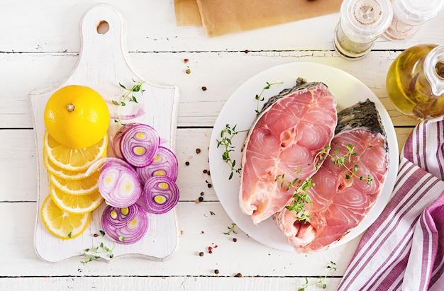 Bife cru de peixe carpa com limão e tomilho na superfície de madeira branca. preparando o peixe para assar em papel manteiga. menu de dieta. vista do topo. configuração plana