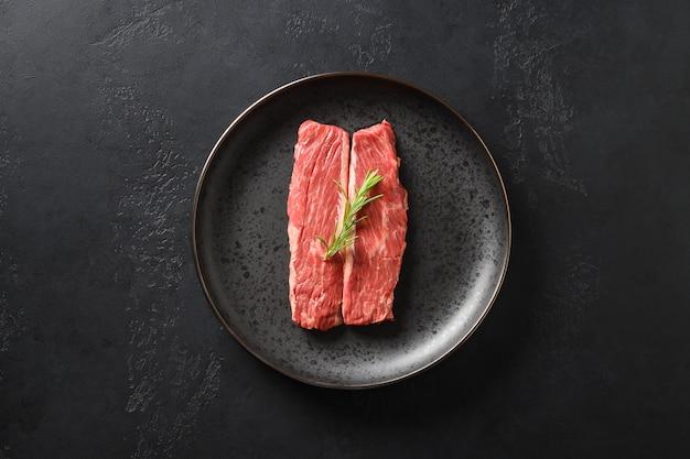 Bife cru do ribeye na placa de corte com alecrins no fundo preto.