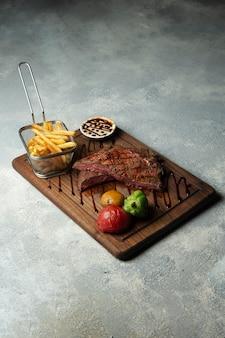 Bife cru médio com batatas fritas e legumes