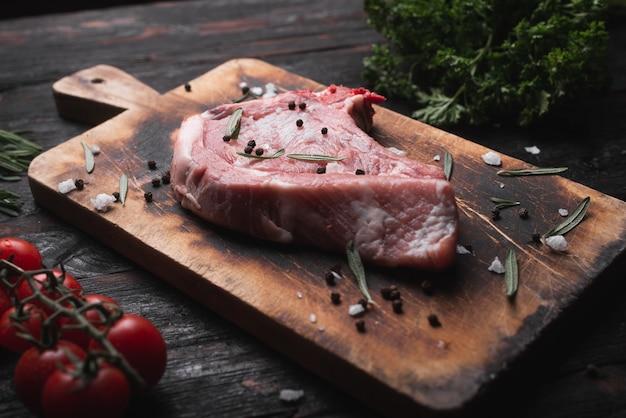 Bife cru na mesa, carne fresca sobre uma tábua de cortar, temperos perfumados para carne