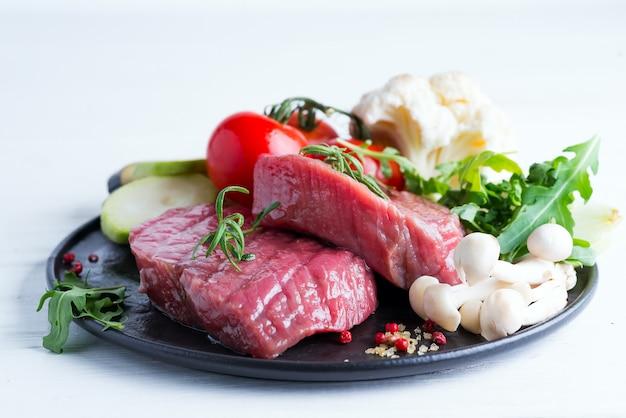 Bife cru no osso com legumes frescos em uma panela sobre um fundo branco, vista superior