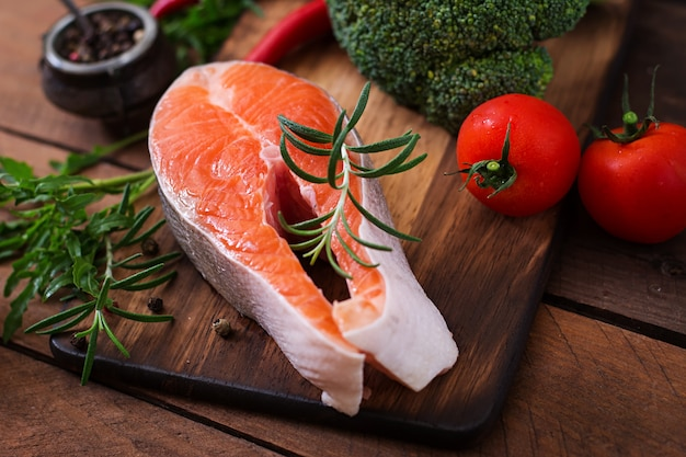 Bife cru salmão e legumes para cozinhar na mesa de madeira em estilo rústico.
