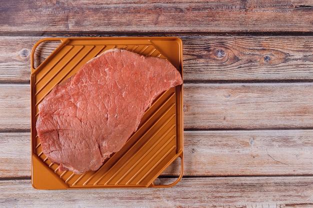 Bife cru vermelho orgânico em uma mesa de madeira.