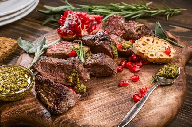 Bife da carne do canguru com pesto e a romã verdes na placa de corte de madeira.