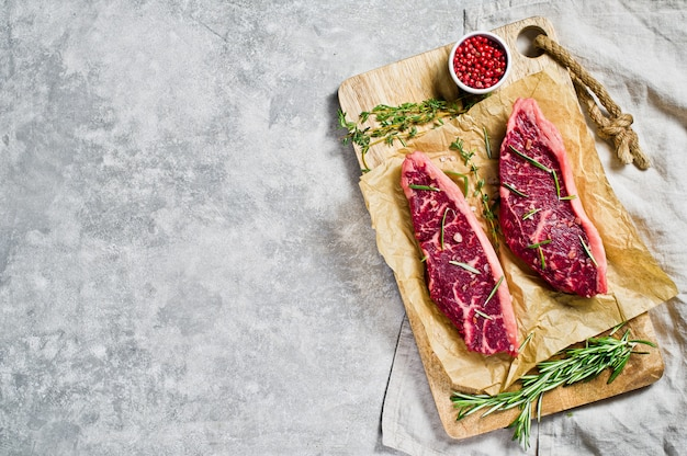 Bife da rampa de carne em uma placa de desbastamento de madeira com alecrins e pimenta cor-de-rosa. copyspace