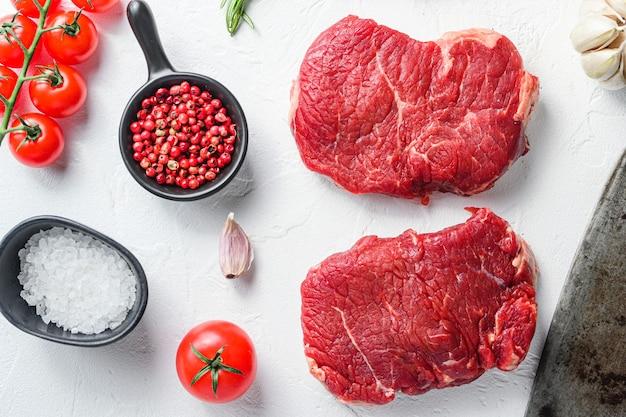 Bife de alcatra cru, carne bovina da fazenda com temperos, alecrim, alho e cutelo de açougueiro