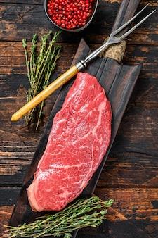Bife de alcatra cru, carne bovina. fundo de madeira escuro. vista do topo.