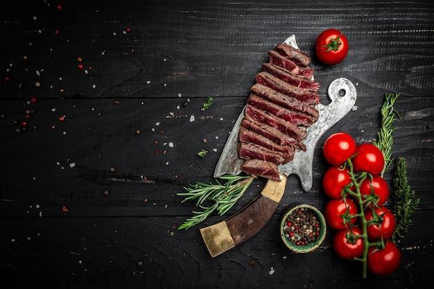 Bife de alcatra suculento bife de carne mal passado servido no velho açougueiro de carne no fundo escuro de madeira. banner, lugar de receita de menu para texto, vista superior.