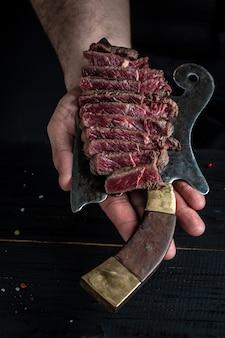 Bife de alcatra suculento de bife de mármore mal passado servido em açougueiro de carne velha, close-up. cozinhar bife de carne pela mão do chef.