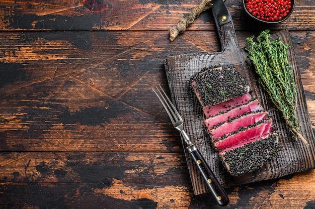 Bife de atum com gergelim grelhado de corte caseiro em uma placa de corte.