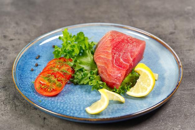 Bife de atum cru com salada e limão no prato azul
