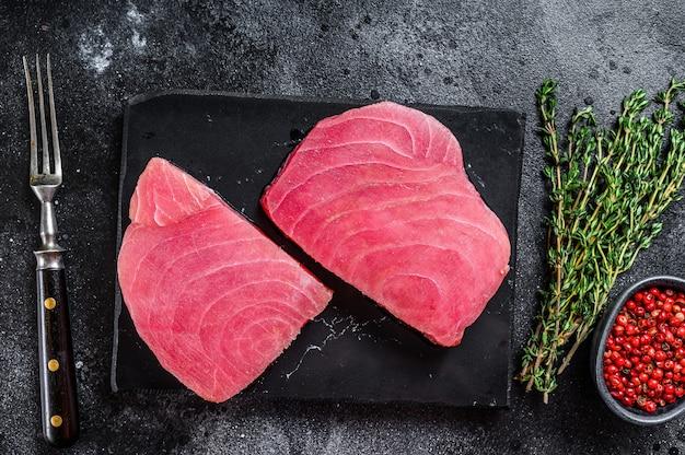 Bife de atum cru em uma tábua de corte de mármore