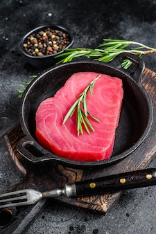 Bife de atum cru fresco com alecrim em uma panela. fundo preto. vista do topo.
