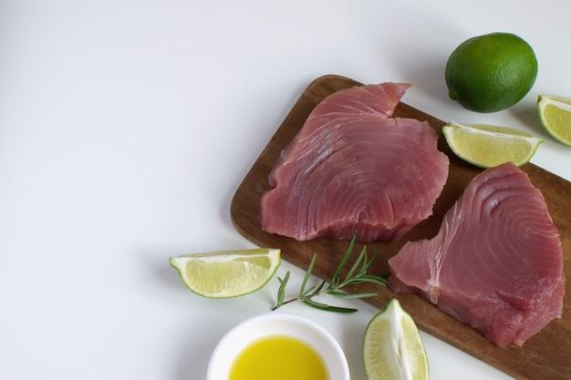 Bife de atum cru tábua de madeira fatia de limão azeite alecrim