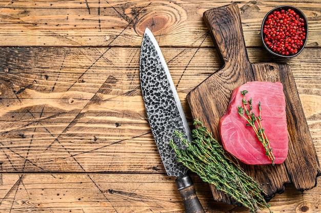 Bife de atum fresco e cru em uma tábua de madeira com faca