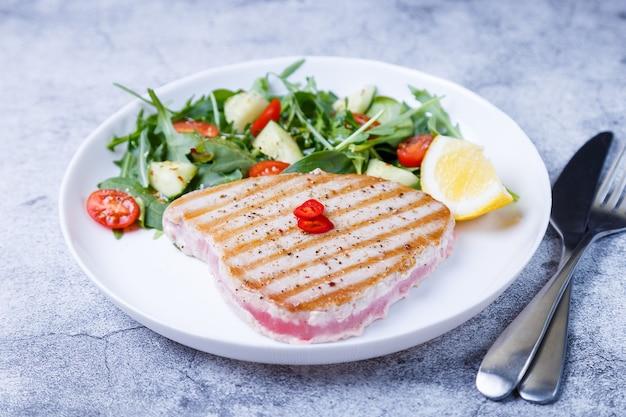 Bife de atum grelhado com legumes frescos, rúcula, espinafre e limão. fechar-se.