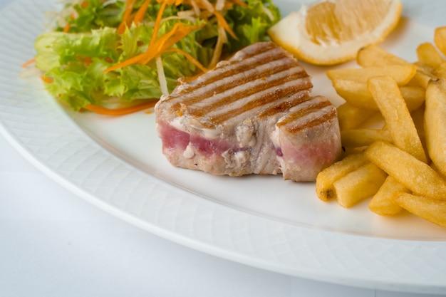 Bife de atum grelhado com salada de batata frita de cenoura, nabo, alface e limão na chapa branca sobre fundo branco.