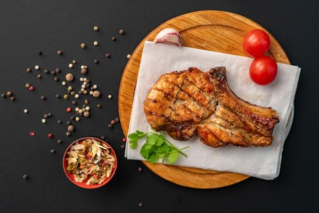 Bife de carne assada quente assado com molho vermelho, cebola e especiarias, folhas de alface