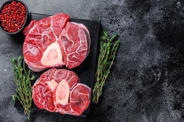 Bife de carne bovina crua bife de osso buco pernil, ossobuco italiano. fundo preto. vista do topo. copie o espaço.