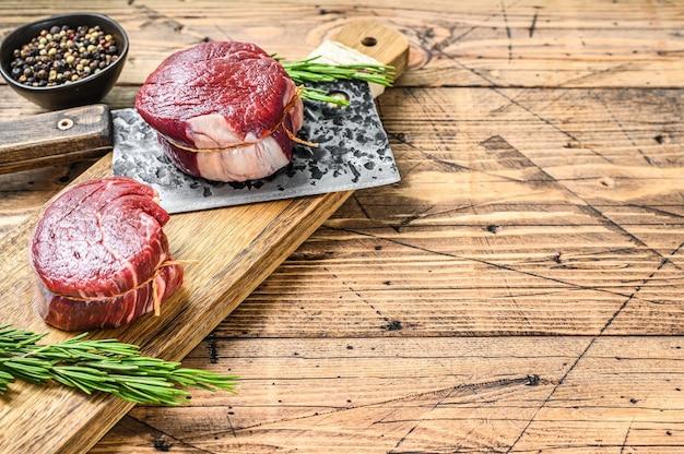 Bife de carne bovina crua filé de lombo. fundo de madeira. vista do topo. copie o espaço.