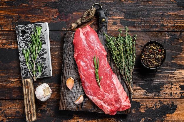 Bife de carne bovina de facão de saia crua em uma placa de corte com cutelo. fundo de madeira escuro. vista do topo.