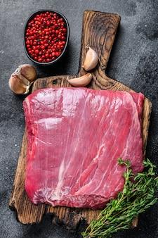 Bife de carne bovina de flanco ou flap cru em uma tábua de madeira. fundo preto. vista do topo.