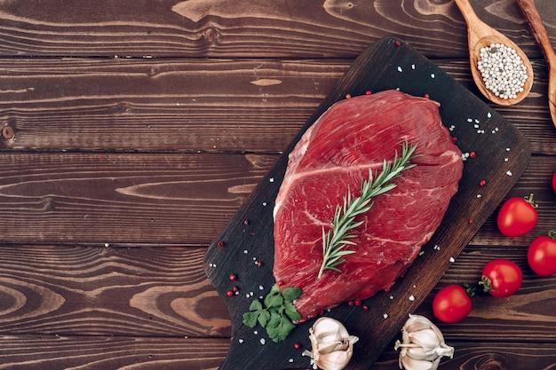 Bife de carne crua com alecrim e especiarias na placa de madeira close-up