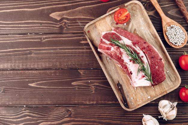 Bife de carne crua com alecrim e especiarias na tábua de madeira