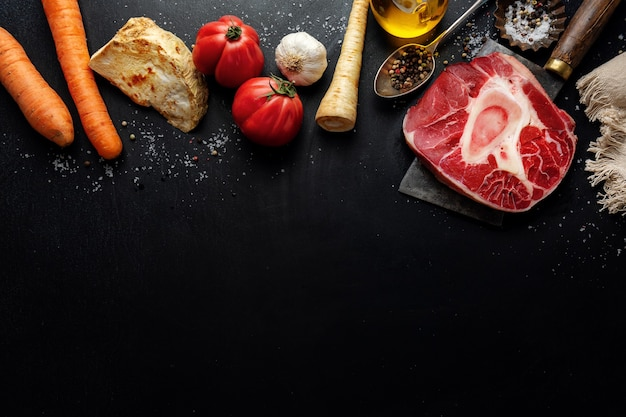 Bife de carne crua com especiarias de osso e vegetais na superfície escura
