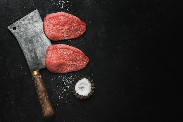 Bife de carne crua com sal e faca de açougueiro no fundo escuro do vintage. vista de cima.