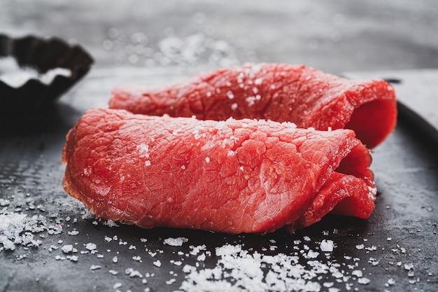 Bife de carne crua com sal no fundo escuro do vintage. fechar-se.
