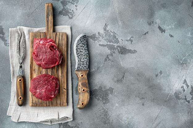 Bife de carne crua. conjunto de carne preta angus prime, em tábua de madeira