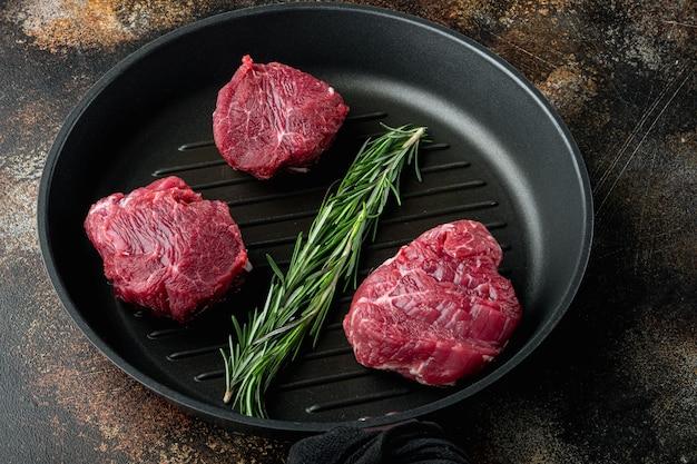 Bife de carne crua. conjunto de carnes pretas angus prime, filé mignon cortado, em frigideira de ferro fundido, em mesa rústica velha e escura