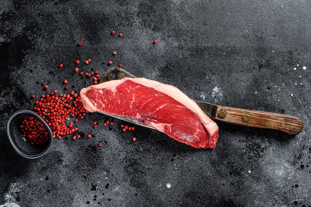 Bife de carne crua em mármore. carne angus preta. fundo preto
